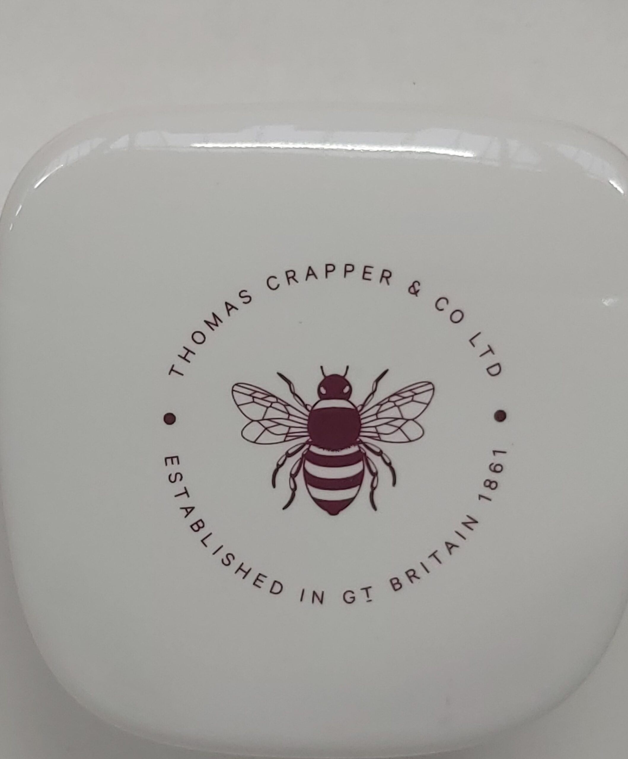 Urinal waste cover showing the 'Crapper Bee' logo